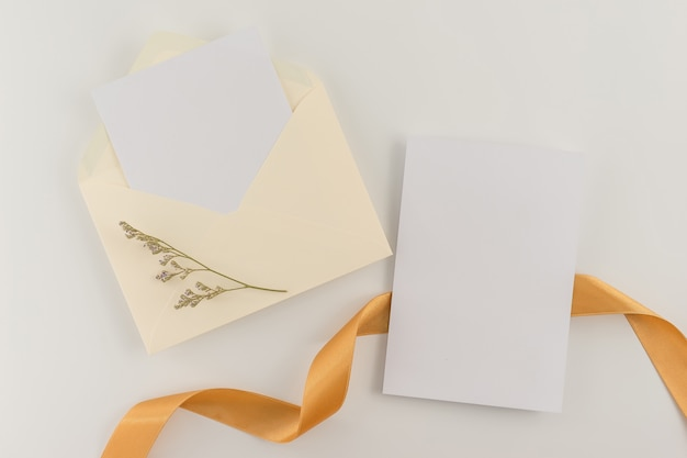 Top view, flat lay, wedding invitation card, envelopes, cards papers on white background.