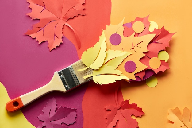 Top view on flat lay with brush loaded with paint made from paper autumn leaves