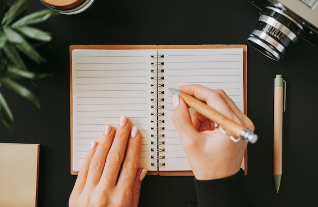 Top view of flat lay woman's hand writes down addresses in an open notebook lying on black table next to camera with pen and notepad