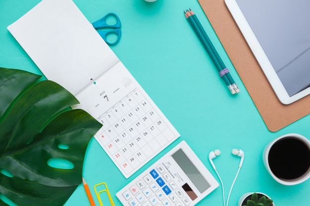 Top view flat lay of workspace desk styled design office supplies with calendar
