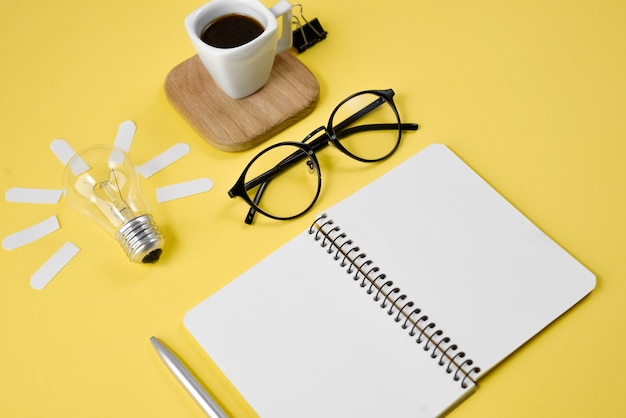 Top view flat lay of workspace desk styled design office supplies with pen, notepad, eyeglasses, cup coffee