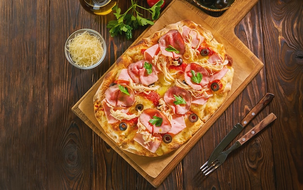 Top view of flatbread pizza with ham on a dark wooden table