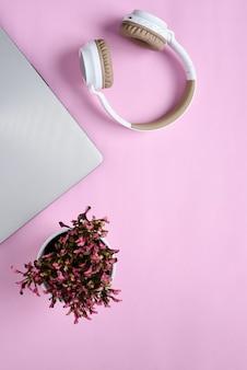 モダンなワイヤレスヘッドフォン、ミニマリストのラップトップ、ピンク色のワークスペースにかわいい紫色の花の上面図フラットレイ
