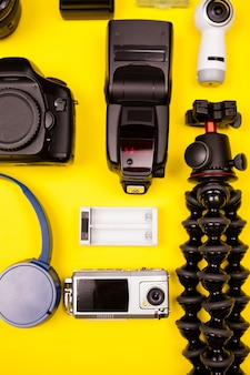 Плоский вид сверху комплекта для фотографа летних каникул на желтом фоне