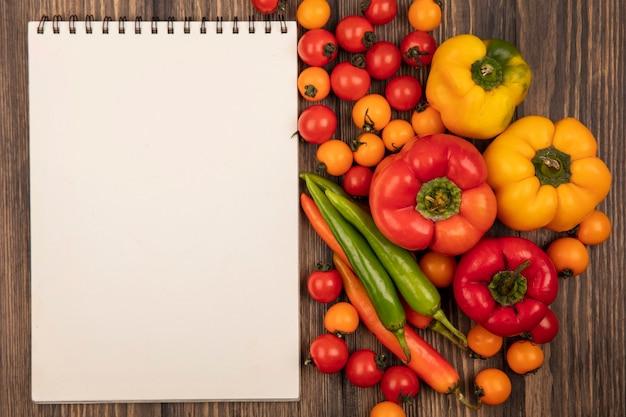 Vista dall'alto di verdure aromatizzate come pomodorini e peperoni isolati su una superficie in legno con spazio di copia