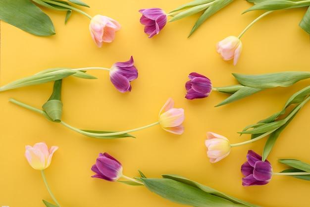 黄色の背景にピンクと紫のチューリップの花の背景の上面図