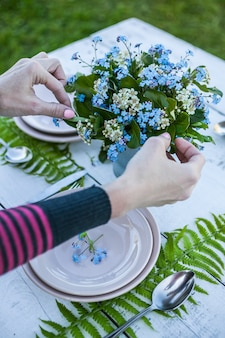 Top view florist makes a bouquet of forget-me-not flowers and fern leaves.