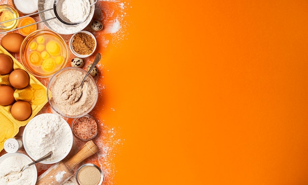 Top view of flour, eggs, butter, sugar and kitchen utensils on orange background
