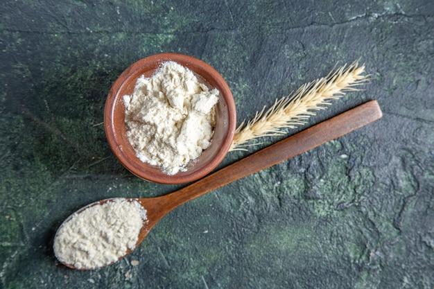 Вид сверху муки внутри коричневого горшка с деревянной ложкой на темном столе