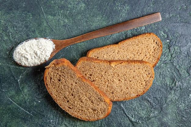 暗い机の上に暗いパンの塊と木のスプーンの上のビュー小麦粉