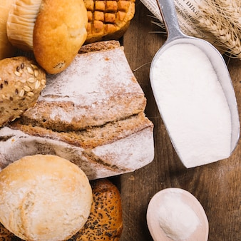 Top view of flour in shovel with baked whole breads and cake on wooden table