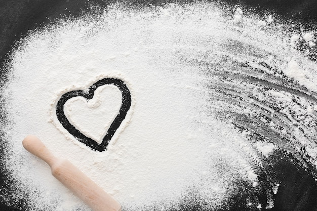 Top view of flour with heart shape and rolling pin