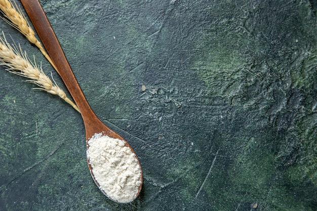 Farina vista dall'alto sul cucchiaio di legno sulla scrivania scura