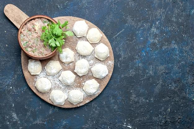 Vista dall'alto di pezzi di pasta infarinata con verdure di carne macinata sulla scrivania scura, pasta per la cena a base di carne cruda