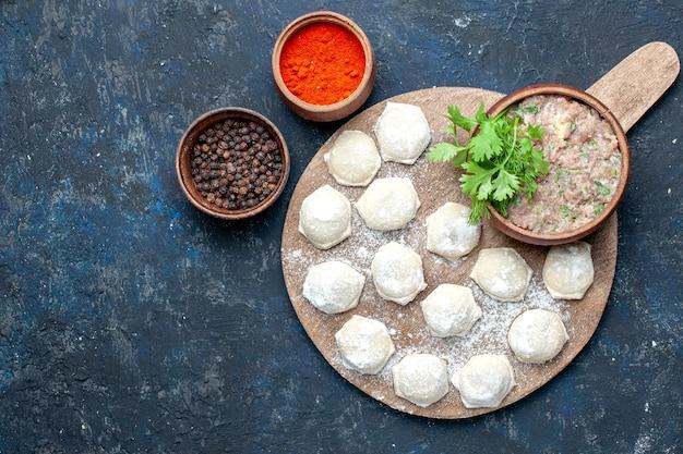 Vista dall'alto di pezzi di pasta infarinata con verdure di carne macinata e peperoni su pasta cena carne cruda scura, pasta alimentare
