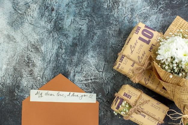 복사 장소와 어두운 배경에 상위 뷰 꽃 꽃다발 선물 편지 봉투