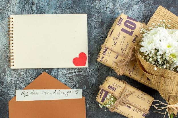 어두운 배경에 상위 뷰 꽃 꽃다발 선물 노트북 편지 봉투