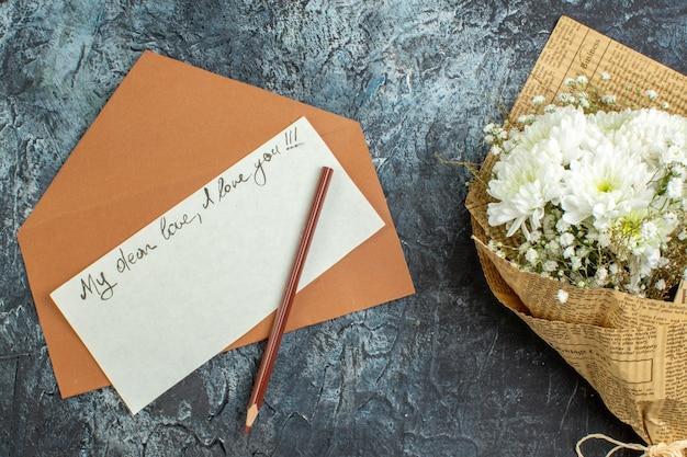 어두운 배경에 상위 뷰 꽃 꽃다발 연애 편지 봉투 연필