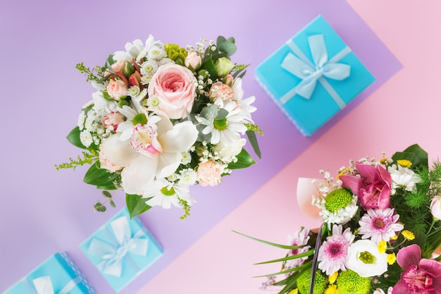 Top view flower bouquet on purple background with presents flat lay