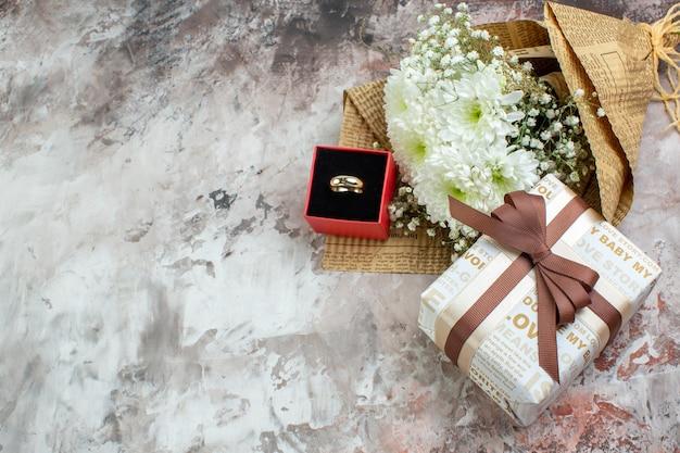 Вид сверху букет цветов кольцо в маленькой коробке подарок на столе со свободным пространством