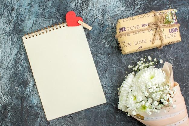 Вид сверху букет цветов обернутый подарочный блокнот с маленькой наклейкой в виде красного сердца на темном фоне
