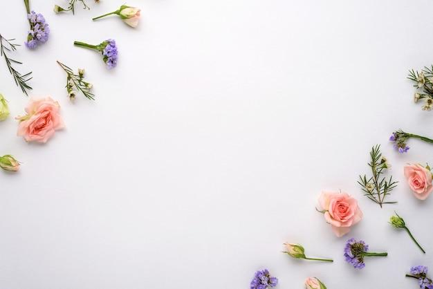 白い背景、ピンクのバラ、トルコギキョウ、コーナーのリモニウム、フラットレイ、コピースペース、花序の概念上の上面の花の構成