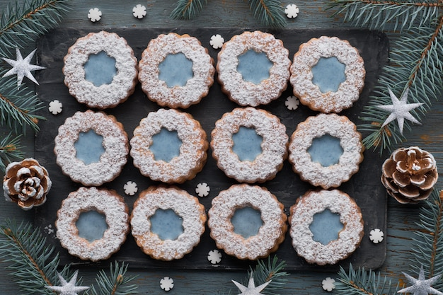 Top view of flower linzer cookies with blue glazing on dark winter background