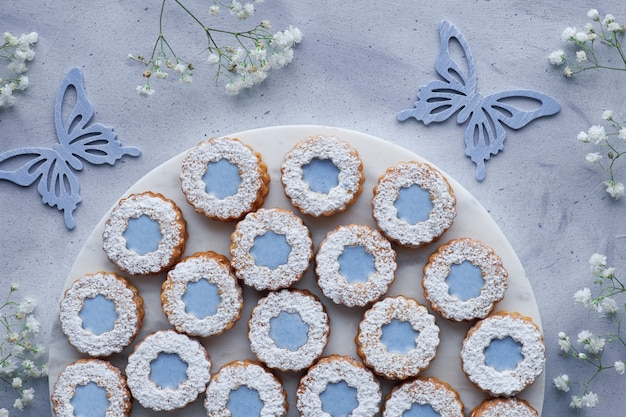 Top view of flower linzer cookies with blue glazing on light