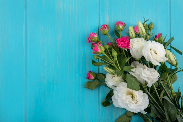 Top view of flowers on blue background with copy space