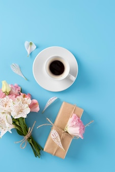 Top view of flowers bouquet with gift and coffee cup