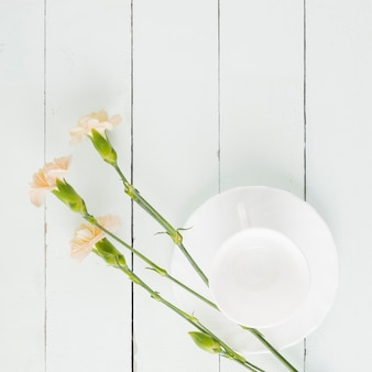 Top view flowers and cup on wooden background