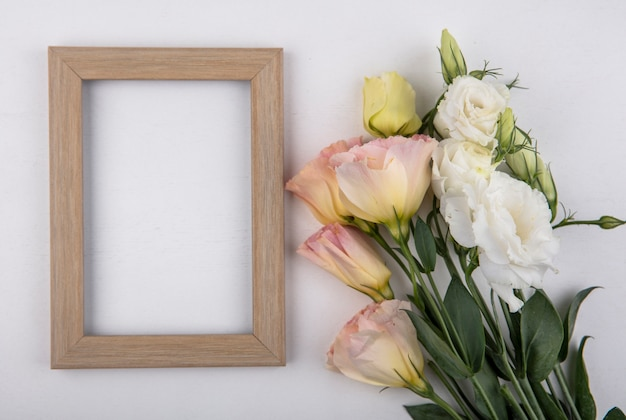 Top view of flowers and frame on white background with copy space