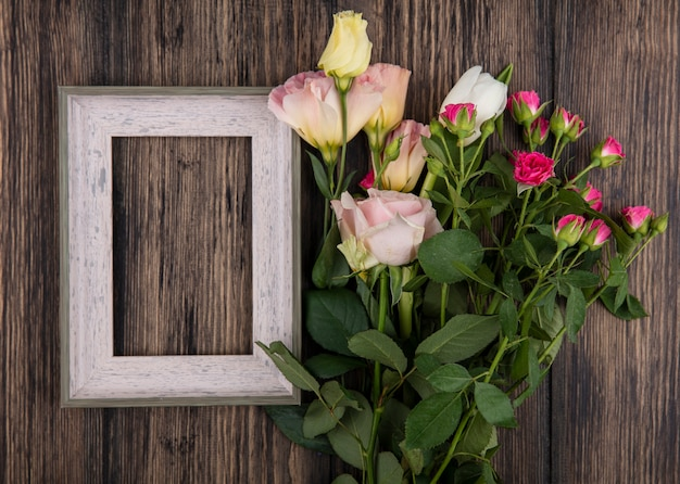 Top view of flowers and frame on wooden background with copy space