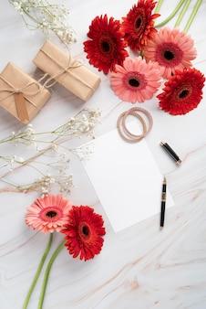 Vista dall'alto di fiori con carta bianca e regali