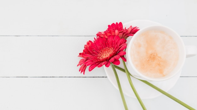 Top view flowers with cup on wooden background