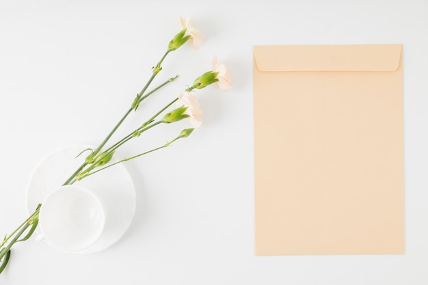 Top view flowers with envelope and cup
