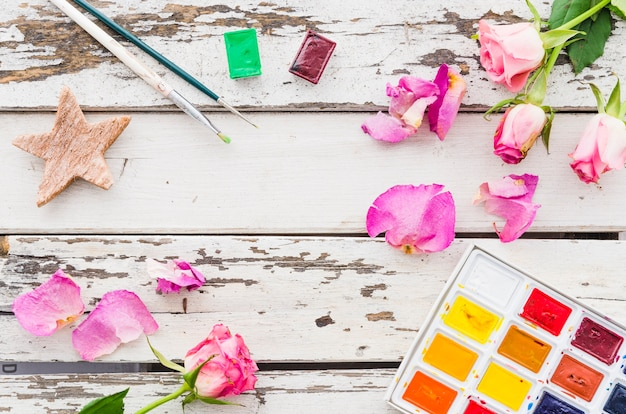 Top view flowers with painting material on wooden table