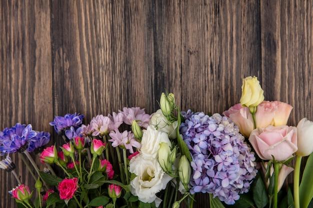 Vista dall'alto di fiori su fondo in legno con spazio di copia