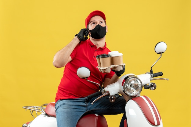 Top view of focused delivery guy wearing uniform and hat gloves in medical mask sitting on scooter showing orders