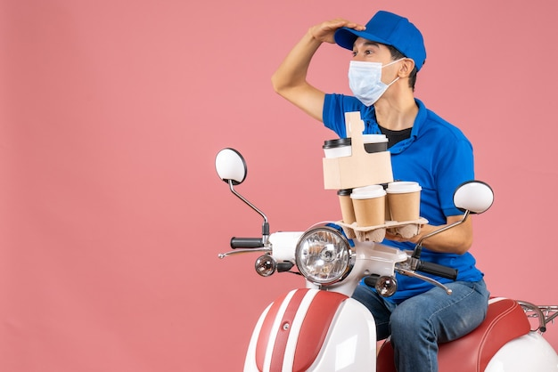 Top view of focused male delivery person in mask wearing hat sitting on scooter delivering orders on peach background
