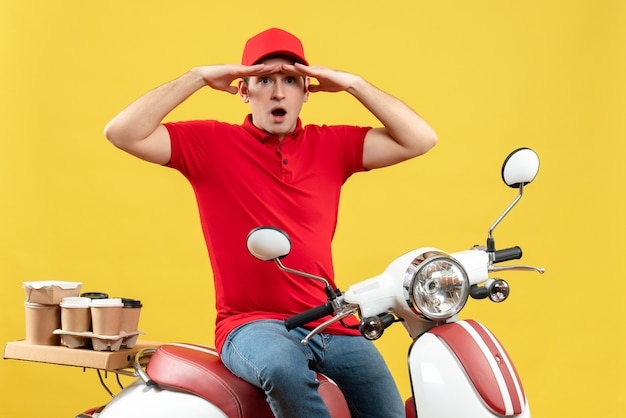 Top view of focused young guy wearing red blouse and hat delivering orders on yellow background