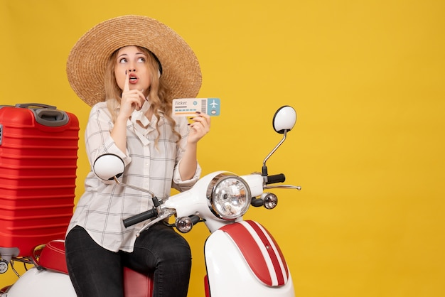 Top view of focused young woman wearing hat and sitting on motorcycle and holding ticket looking up on yellow