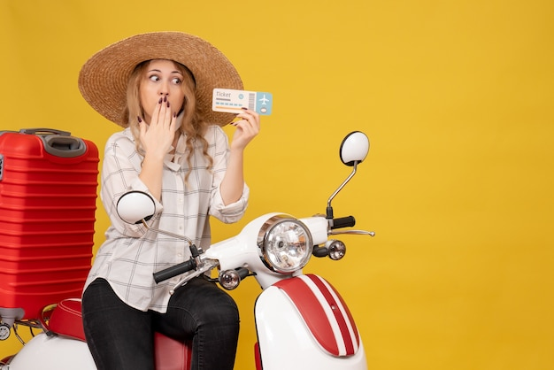 Top view of focused young woman wearing hat and sitting on motorcycle and holding ticket on yellow