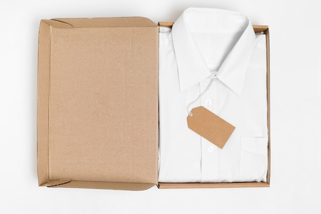 Camicia piegata vista dall'alto e etichetta riciclabile in una confezione di cartone