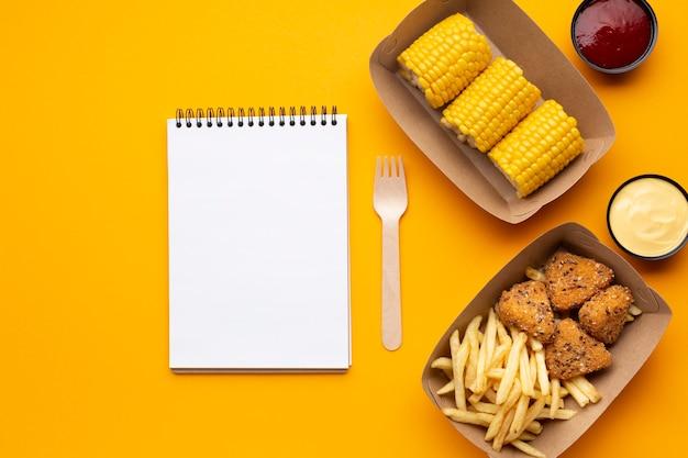Top view food arrangement with notebook