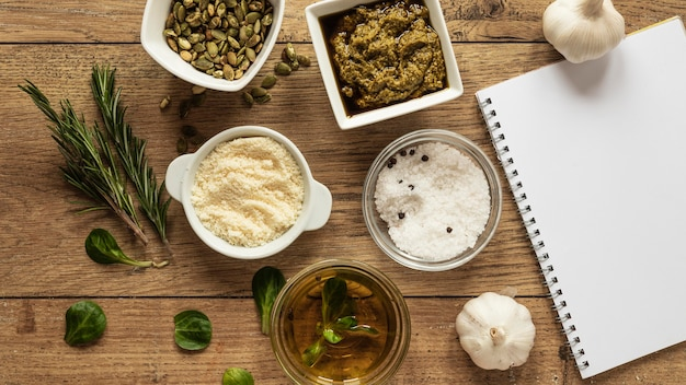 Top view of food ingredients with notebook and herbs