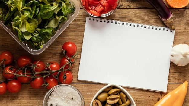Vista dall'alto di ingredienti alimentari con taccuino e verdure