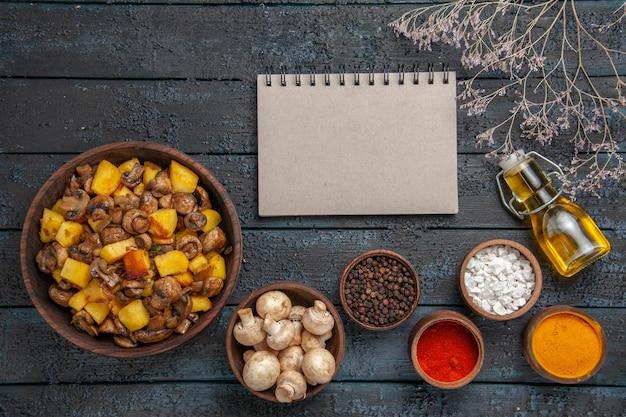 白いキノコのボウルの横にあるジャガイモとキノコのテーブルプレート上の上面図食品ノートブックさまざまなスパイスとボトルに入ったオイル