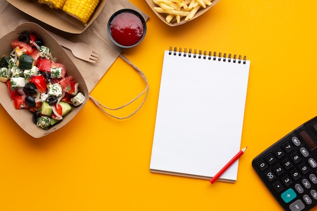 Top view food with notebook on yellow background