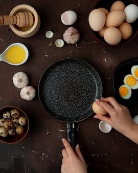 Vista dall'alto di alimenti come burro aglio uovo con padella e donna mano frenando uovo su sfondo marrone